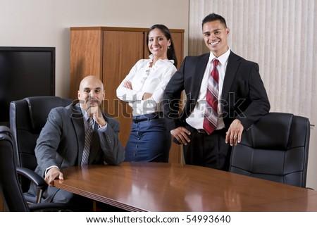 Three Hispanic business people smiling in boardroom - stock photo
