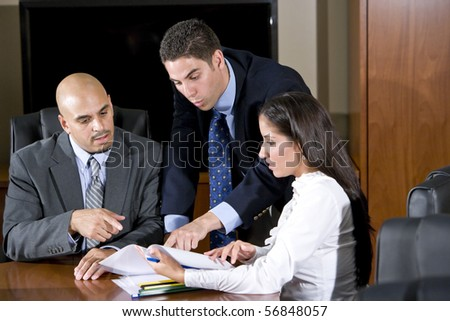 Three Hispanic office workers reviewing report - stock photo