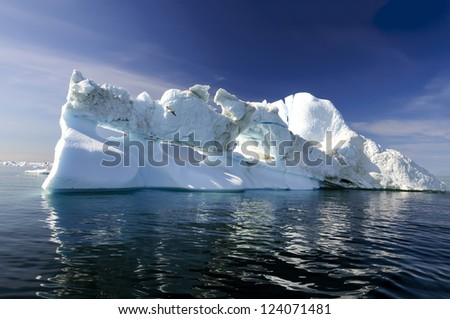 Three holes iceberg floating in Disko Bay near Ilulissat, Greenland. An iceberg is a large piece of freshwater ice that has broken off a glacier or an ice shelf and is floating freely in open water. - stock photo