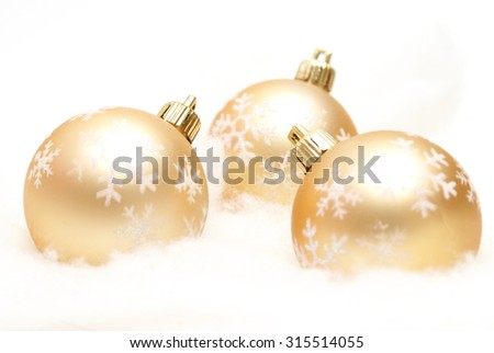 Three holiday baubles on some fake snow. - stock photo