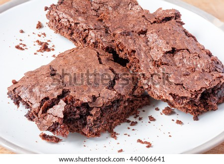 Three home-made chocolate brownies on a white plate - stock photo