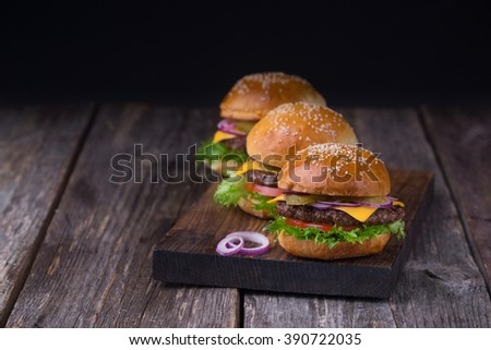 Three homemade burgers with beef patty, lettuce, tomato, cheese, pickled cucumbers and red onion served on wooden cutting board - stock photo