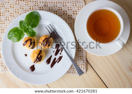 Three homemade coconut cookies with dripped dark chocolate and fresh mint leaves. Sweet afternoon with tea. Top view - stock photo