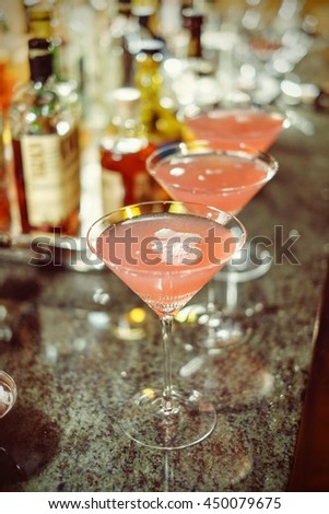 Three Homemade Cosmopolitan cocktails on a bar counter in a home served in Martini crystal glasses - stock photo