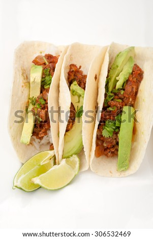 three homemade soft tacos with ground meat, avocados, cilantro and rice isolated on white background, room for text
