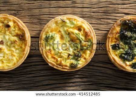 Three homemade vegetable quiche's sitting on a rustic wooden background.