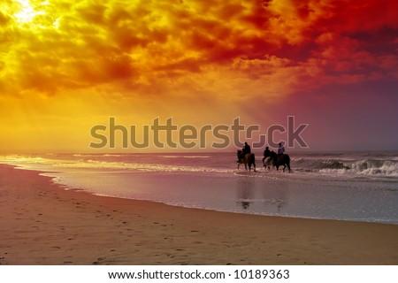Three horse riding seniors on the beach. - stock photo