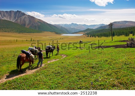 Three horses, two mens and mountains. Altay. Russia. - stock photo