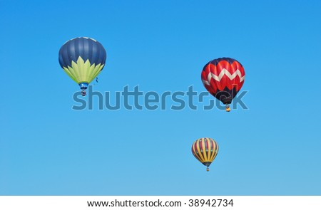 Three hot air balloons against a blue sky - stock photo