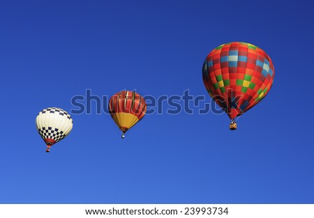 Three hot air balloons ascending into the beautiful blue sky.