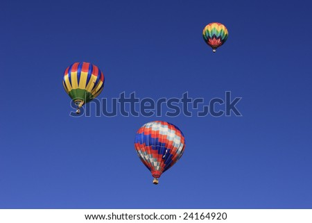 Three hot air balloons floating across a picture perfect blue sky.