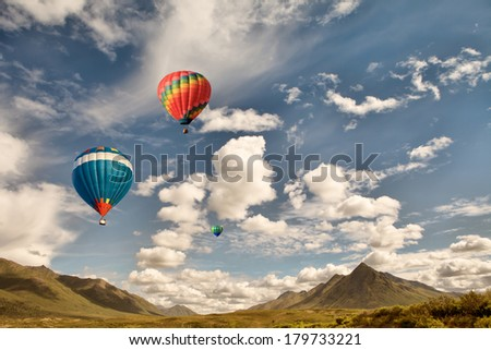 Three hot air balloons flying over mountain wilderness in Canada with puffy clouds and blue sky. - stock photo