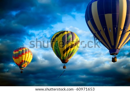 Three hot air balloons  lift off at sunrise, sunset  drifting on air currents. Flying before a dramatic background of clouds and bright blue sky.  Original illustration. - stock photo