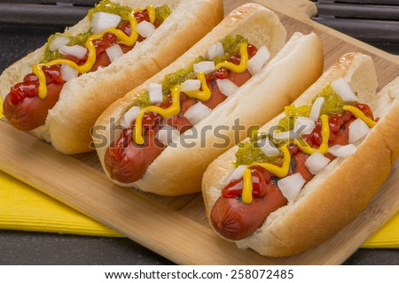 Three Hot Dogs with Mustard, Ketchup, pickle relish and onions   - stock photo