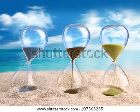 Three hourglass in the sand with blue sky - stock photo
