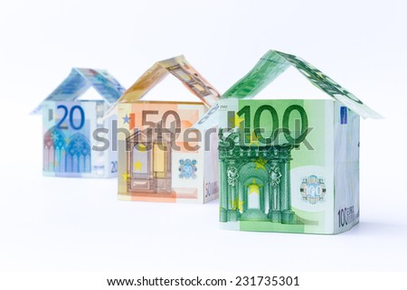 Three houses made of euro notes isolated on white background - stock photo