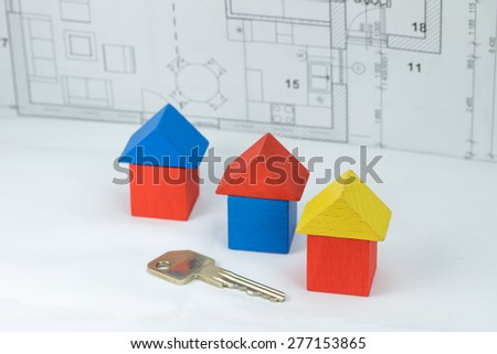 Three houses made of wooden multicolored shapes are standing in front of the blueprint of the house. Before them lies the key to the house.