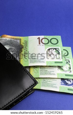 Three hundred Australian dollar green and yellow notes folding out from black wallet. Vertical. - stock photo