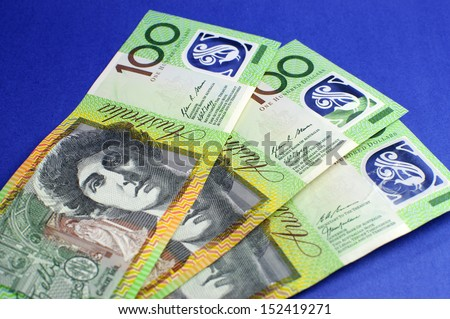 Three hundred Australian green and yellow notes on blue background. - stock photo