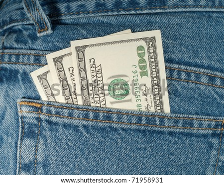 Three hundred dollar bills stick out of a denim jeans pocket