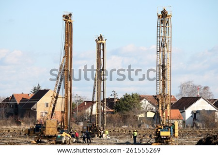 three hydraulic drilling machines and workers on construction site - stock photo