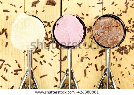 three ice cream scoops on wooden surface