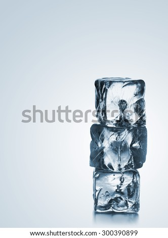 Three ice cubes stacked over blue gradient background with copy space - stock photo