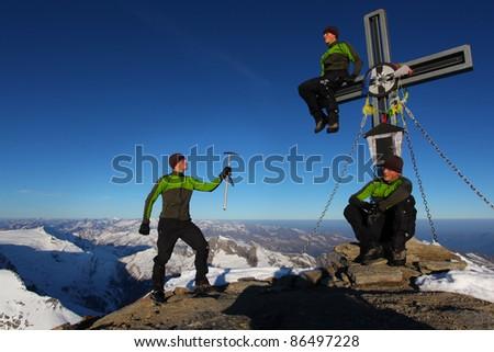 Three identical man on a mountain summit - stock photo