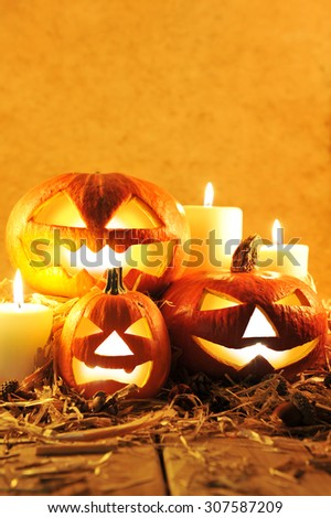 three illuminated halloween pumpkins and straw on old weathered wooden board in front of orange background in candlelight - stock photo