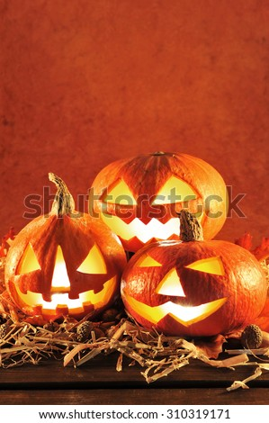 three illuminated halloween pumpkins in red light and straw on old weathered wooden board in front of brown background - stock photo
