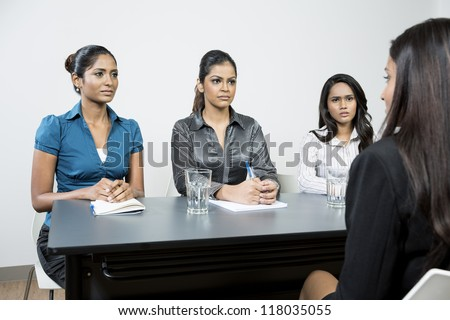 Three Indian colleagues from hr department interview a female applicant - stock photo