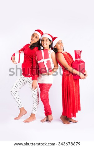 three indian girls with red cloths and santa hat holding gifts, isolated on white, asian teenage girls and christmas, standing