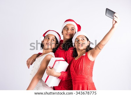 three indian girls with red cloths and santa hat holding gifts, isolated on white, asian teenage girls and christmas, standing and posing for a selfie with mobile in one hand - stock photo