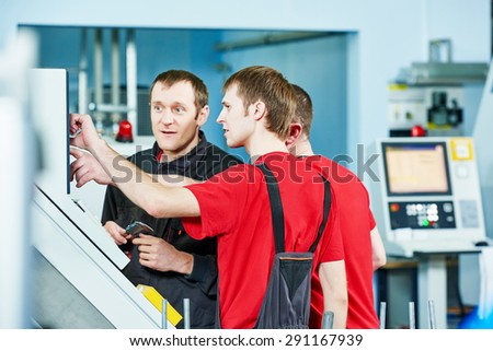 three industrial workers at cnc turning machine center in tool manufacture workshop - stock photo