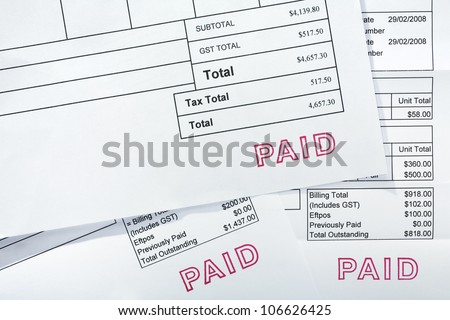 Three invoices for several thousand dollars, all with PAID stamp. These are normal bills, with folds and a few creases. - stock photo