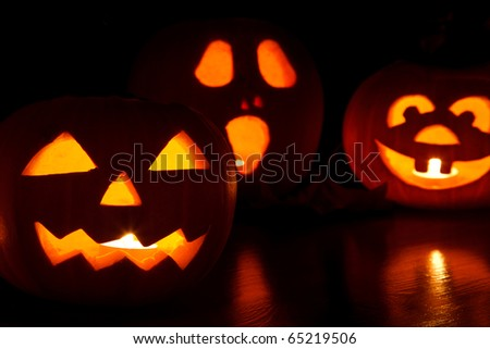 three jack-o-lantern pumpkins glowing in the dark - stock photo