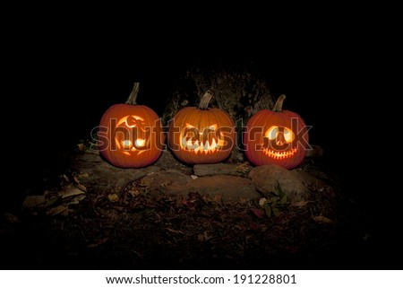 Three jack-o-lanterns sit on the ground outdoors, lighting the night. They are lit with candles and a light painting technique was used to provide additional light to the scene. - stock photo