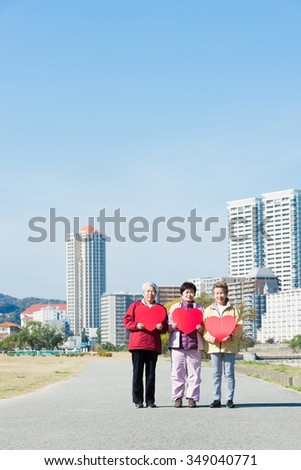 Three Japanese elderly people standing with a red heart mark