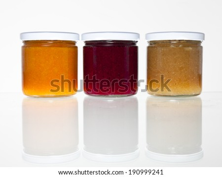 Three jars full of fresh homemade colorful jams or marmalade in glass containers with a reflection on a glass table against a white background. - stock photo