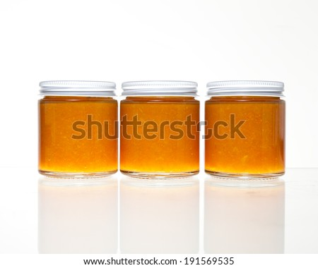 Three jars full of fresh homemade colorful jams or marmalades in glass containers with a reflection on a glass table against a white background.