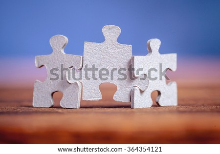Three jigsaw puzzle pieces on a table joint together over blue background. Shallow depth of field