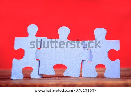 Three jigsaw puzzle pieces over red background - stock photo