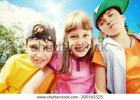 Three joyful children looking at the camera against the blue sky. Summer. - stock photo