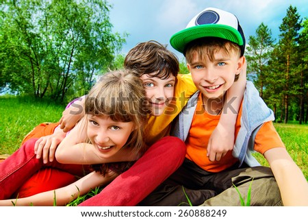 Three joyful children sitting on the grass in the park. Summer. - stock photo