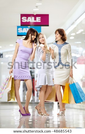 Three joyful girlfriends in shop with a credit card and bags - stock photo