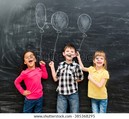 three joyful laughing children keep imaginary balloons drawn on the chalky blackboard - stock photo