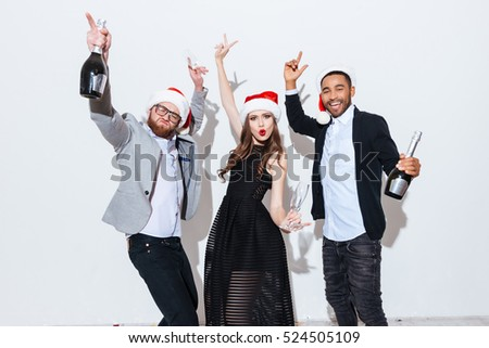 Three joyful people in santa claus hats having party and dancing over white background
