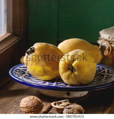 Three juicy quinces in blue ceramic plate, walnuts and jar of honey over wooden table near window with bright sunlight. Dark rustic style. Square image with selective focus - stock photo