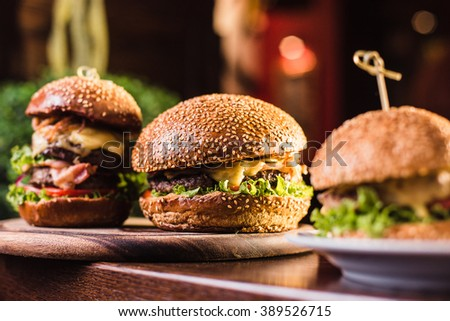 Three juicy tasty burger on the white plate on a dark background - stock photo