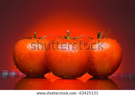 Three juicy tomatoes on a red background - stock photo